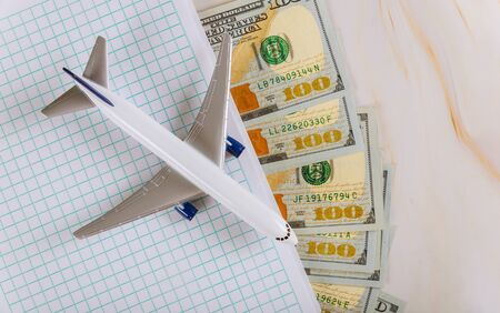 Travel, planning notebook with airplane, holiday tourism US dollar banknotes with airplane