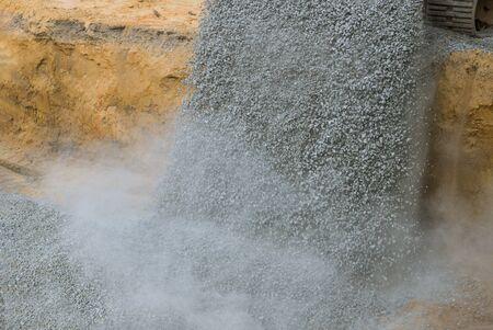 Excavator unloading gravel at construction work equipment machinery for construction of foundation 版權商用圖片