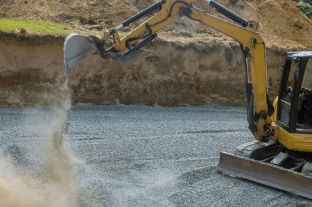 A excavator in a working to gravel construction equipment for foundation construction of residential building 写真素材