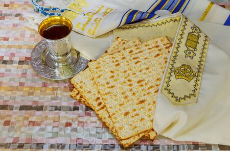Jewish Pesah celebrating, matzoh and traditional seder plate with tallit, Passover holiday