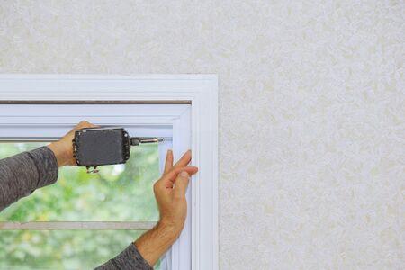 Ouvrier du bâtiment installant une nouvelle fenêtre une nouvelle maison à ossature en plastique à l'aide d'un tournevis