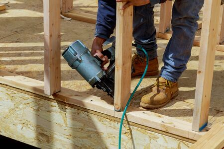 Building contractor worker nailing timber with air nail gun Stock Photo