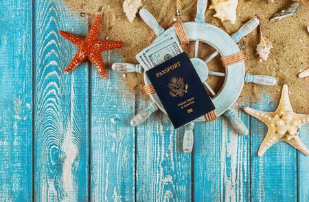 Captain Steering wheel travel concept with money dollar bills on sand star fish and shells US Passport on old blue wooden background