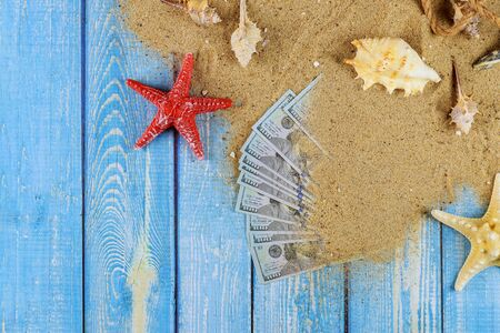 Travel concept with money dollar bills on sand star fish and shells on old blue wooden background Stock Photo