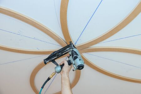 Installation of decorative mouldings on the ceiling carpenter using nail gun molding fragment