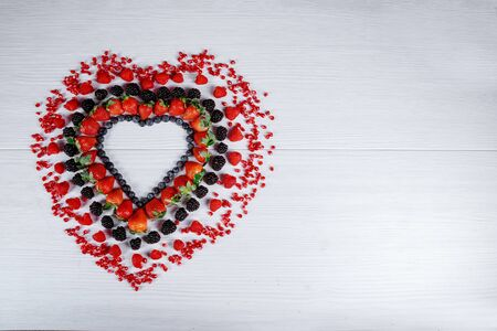 Heart shaped from berries fruit on white table. Valentines day concept.