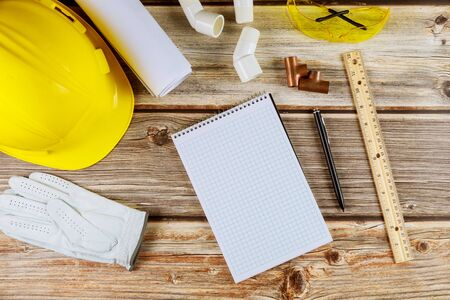 Building construction on blueprints with tools and helmet on notebook with pen with working equipment office desk table