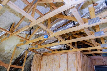 Air conditioning system attached to attic ceiling, foam plastic insulation of a new home HVAC vents being installed