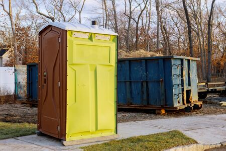 Portable chemical toilets for construction new house and recycling container trash dumpster full garbage
