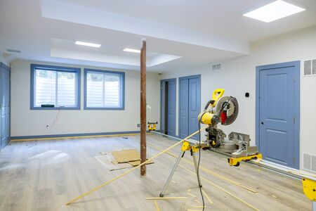 Finishing work in a new home cutting circular saw and nailing wood shoe molding, construction building industry