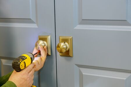 Install door knob with a screwdriver to the room. Reklamní fotografie
