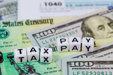 Economic stimul tax return check and 1040 form individual income tax with dollar billsTax Pay Day