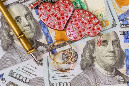 Wedding rings on the background of hundred dollar bills money marriage contract