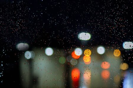 Blurred city street with waterdrops, neon lights car background