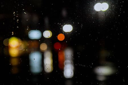 Rain drops on car window with road light bokeh in night in rainy season