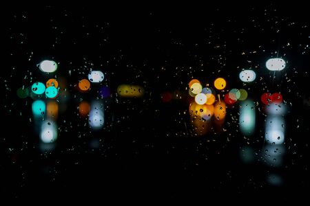 Wet the window with night rain and town lights night city background
