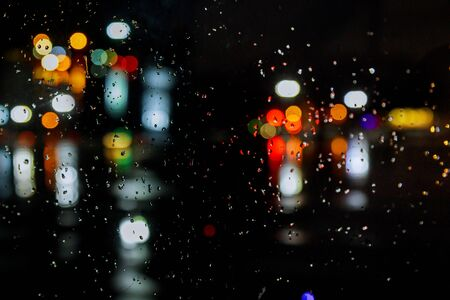 Rain drops on window with road light bokeh city in night rainy season