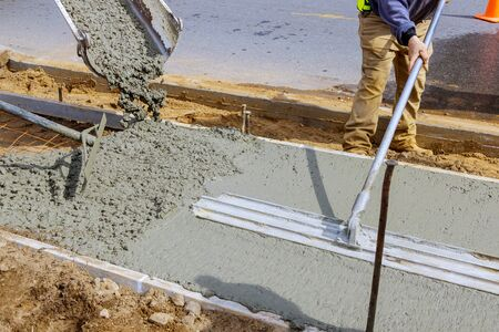 Construction worker pour cement for sidewalk in concrete works with mixer truck with wheelbarrow at construction site filling formwork with cement and gravel