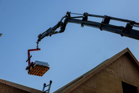 A wooden roof truss being lifted by a boom truck forklift in the roof of a new home