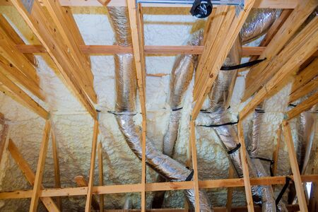 Building with wooden beams of a roof installing pipe heating system a house attic under construction