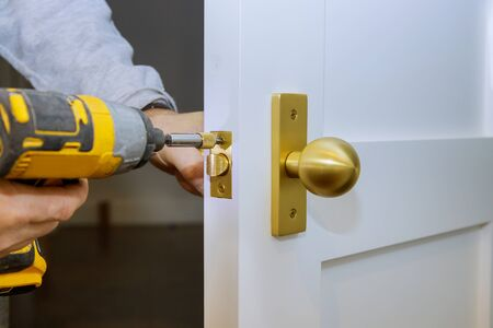 Close up of installation of the door lock with a screwdriver