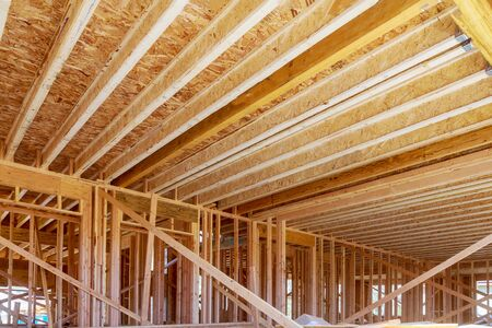 Condominium building with under construction wooden house with timber framing, truss, joist, beam close-up