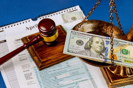 Hundred US dollar bills on a table scales of justice, gavel IRS form. 1040 U.S tax forms calendar while pages April of the deadline time tax season Standard-Bild - 143096687