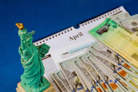 Money and calendar U.S dollars money tax return Statue Liberty in the tax period in the US with 1040 US tax form Standard-Bild - 143096690