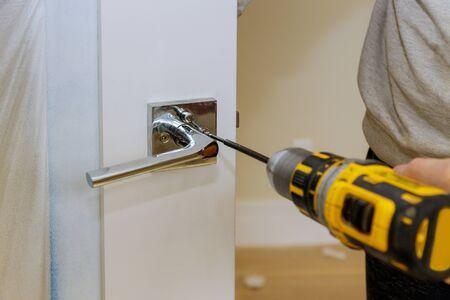 Carpenter installing door lock in the new house with a screwdriver Standard-Bild - 143118554