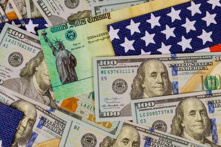 Financial a stimulus bill individual checks from government US 100 dollar bills currency on American flag Global pandemic Covid 19 lockdown