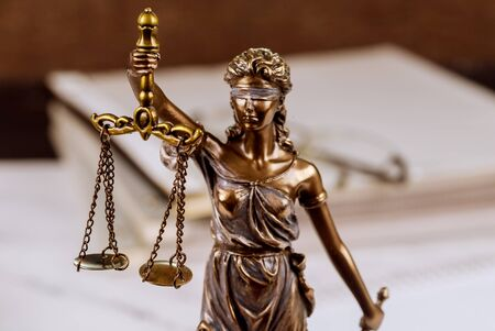 Statue Justice skaliert Anwaltsstapel unvollendeter Dokumente auf dem Schreibtisch der Anwaltskanzlei Standard-Bild