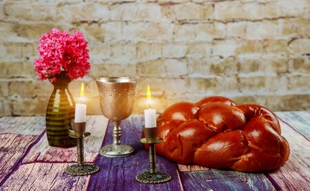 Traditional Jewish Sabbath Shalom ritual fresh challah bread with kiddush cup of red kosher wine
