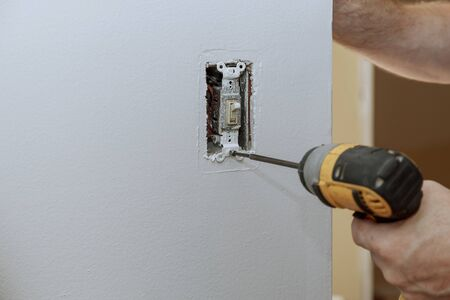 Replacement of the old switch with a new one in closeup of hand of electrician installing wall outlet 스톡 콘텐츠