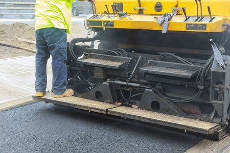 Asphalt paver machine during road construction, road construction the first layer of asphalt.