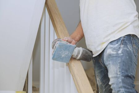 A wooden staircase renovation railing sandpaper sanding for wooden handrails