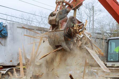 Truck with excavator loads construction waste on a dump truck disposal bin