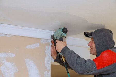 Carpenter using air nail gun to crown moldings trim for ceiling