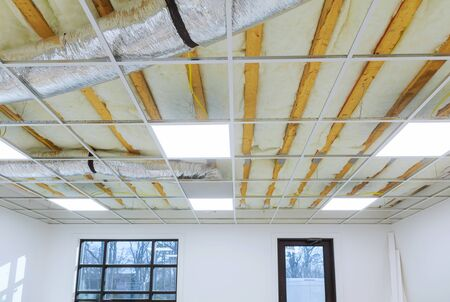 Office room frame hung ceiling at construction of metal rails of a modern built-in lamp ceiling of the room