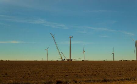 Electric wind turbine windmill installation wind turbine with blue sky background. Standard-Bild