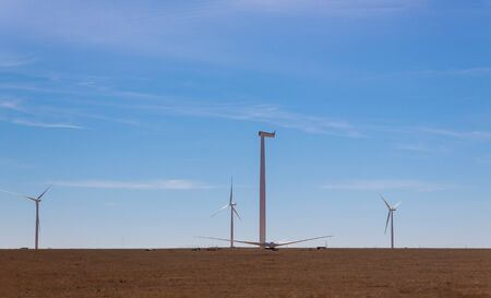 A panoramic view of the windmill in a field installation wind turbine with blue sky background