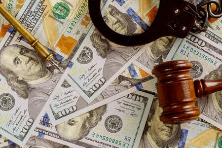 Justice and law concept cash dollars in banknotes judge gavel with handcuffs in court