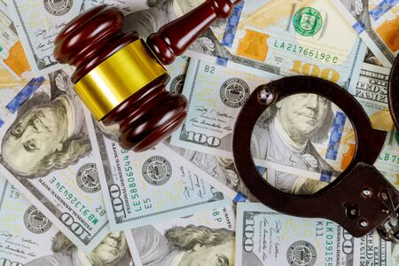 United States dollars bills cash on wooden judge gavel and handcuffs, legal justice desk