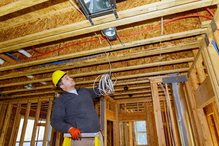 Electrician installing electrical cable wire in new house construction site