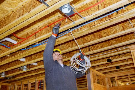 Process of installing electric wiring lights and ceiling in new home new home construction Archivio Fotografico