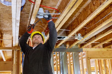 The electrician nailing to the ceiling lamp, installs the lighting lamp in the laying ceiling