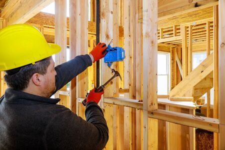 Worker puts on electrical outlets installation in new home