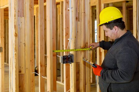 Male electrician technician inspector check inspect electrical system electrician holding tablet PC a house under construction