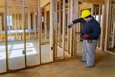 Inspector man inspects house electrical systems electrician holding tablet PC a house under construction