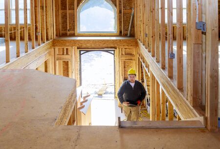 New construction house builder in hard hat walking in the holding tablet PC