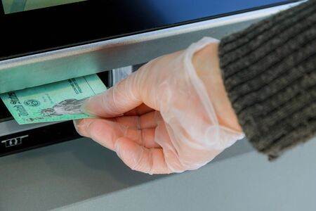 Close up of hand entering deposit stimulus check to ATM machine transfer